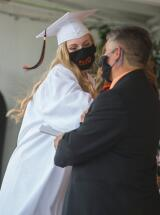 Graduate Lauren Berger elbow bumps with school board president Girard Fewins Sr. during Weatherly's graduation.