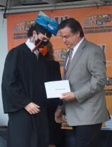 Weatherly school board member Chad Obert give a diploma to his son Chad, Jr. at the school's graduation ceremony.
